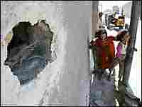 Iraqi girls play outside their damaged home in a ghetto near Najaf's front line,