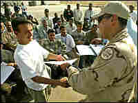 A new Iraqi border patrol police officer (L) receives his certificate. Credit: Reuters