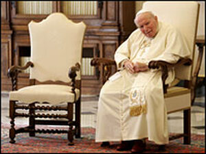 Pope John Paul II, seated at the Vatican.