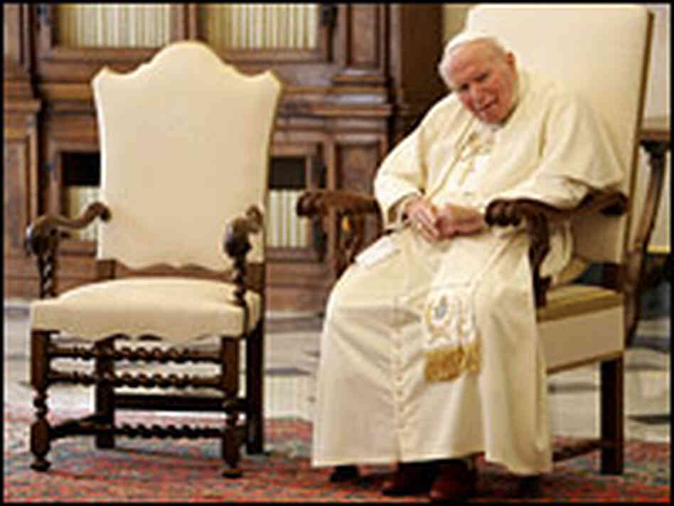 Pope John Paul II, seated at the Vatican.