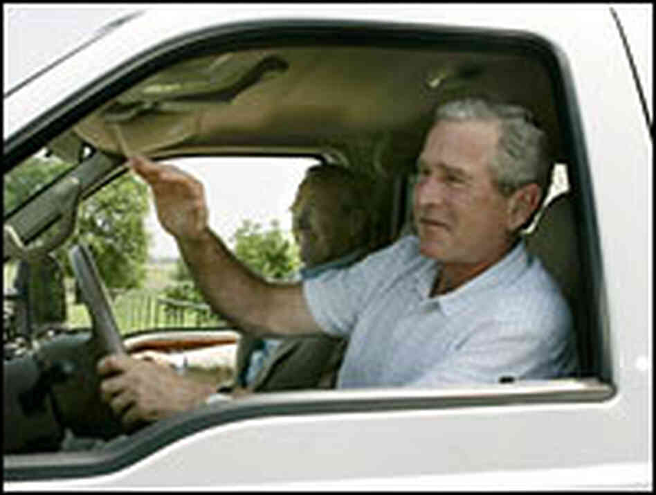 President Bush drives a pickup truck as Defense Secretary Donald Rumsfeld rides along.