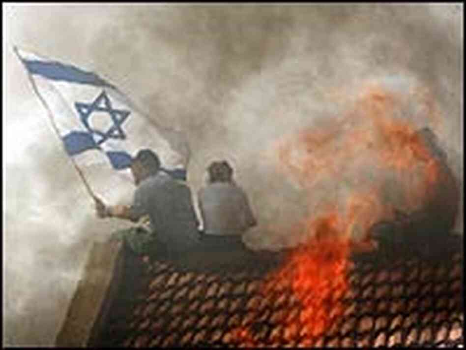 A Jewish settler waves an Israeli flag atop a burning roof in Gadid.
