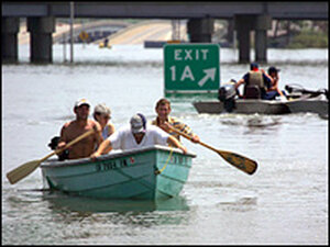 Members of search and rescue teams help evacuate people trapped in flooded homes in New Orleans.