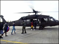 A military helicopter evacuates a family in New Orleans.