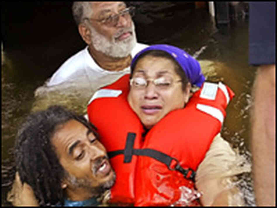 Yolanda Williams (in lifejacket) is rescued by a boat from the doorway of her house.