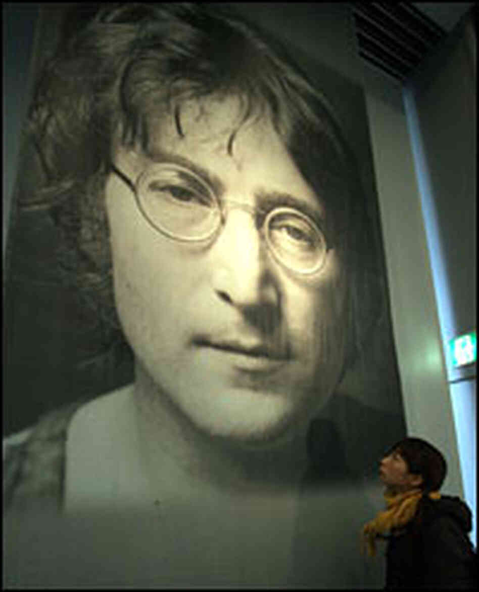 A girl looks at a portrait of John Lennon.