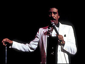 Richard Pryor in white suit, microphone in hand.