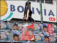 A Bolivian woman walks near election posters in La Paz