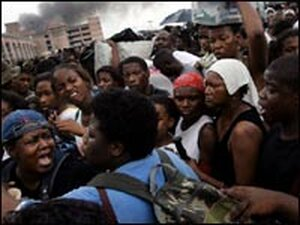 Victims of Hurricane Katrina argue as they line up for buses to evacuate the Superdome and New Orlea