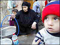 People fill containers with clean water in Baghdad