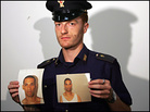 An Italian police officer holds photos of Osman Hussain at the central police station in Rome.