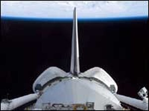 A view of Discovery's cargo bay over Earth's horizon.