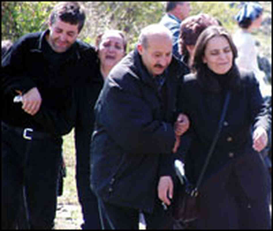 Serbs return from an excavation site that contains the remains of their family members.