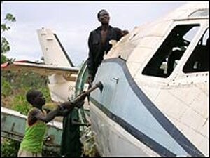 Workers at an airstrip in Rumbek, in South Sudan, hack apart the fuselage of an old transport plane.