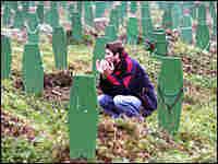 A Bosnian Muslim man prays between graves of victims of Srebrenica massacre in 1995