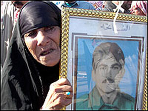 An Iraqi woman carries a picture of her son who was executed after the 1991 Shiite uprising,