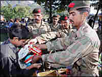 A victim of South Asia's earthquake receives goods from military personnel at Battal in Pakistan