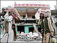 Victims of Pakistan's earthquake carry their belongings in Muzaffarabad
