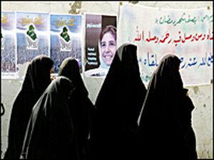 Iraqi women walk past campaign posters promoting the constitutional referendum near Baquba, Iraq