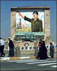 A Saddam propaganda portrait looks down on the people of Tikrit in 1995. Credit: Corbis.