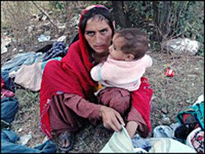 Kashmiri earthquake survivor with goods collected from a distribution center near Muzaffarabad