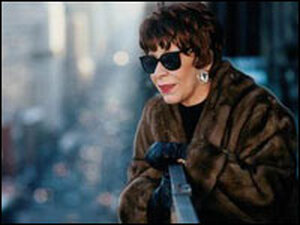 Shirley Horn, in sunglasses and fur coat, peers over a balcony railing.