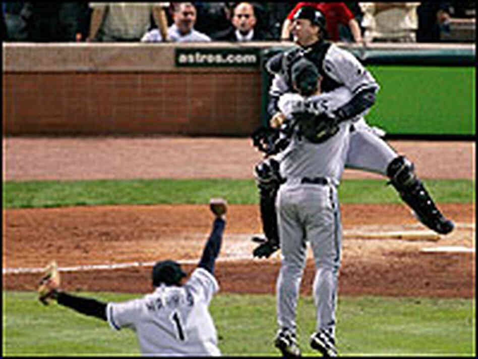 Chicago White Sox catcher A.J. Pierzynski jumps into the arms of pitcher Bobby Jenks.