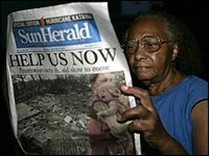 """Resident Mary Mason reads a newspaper with the headline """"Help Us Noin a rescue shelter in Biloxi, Mi"""