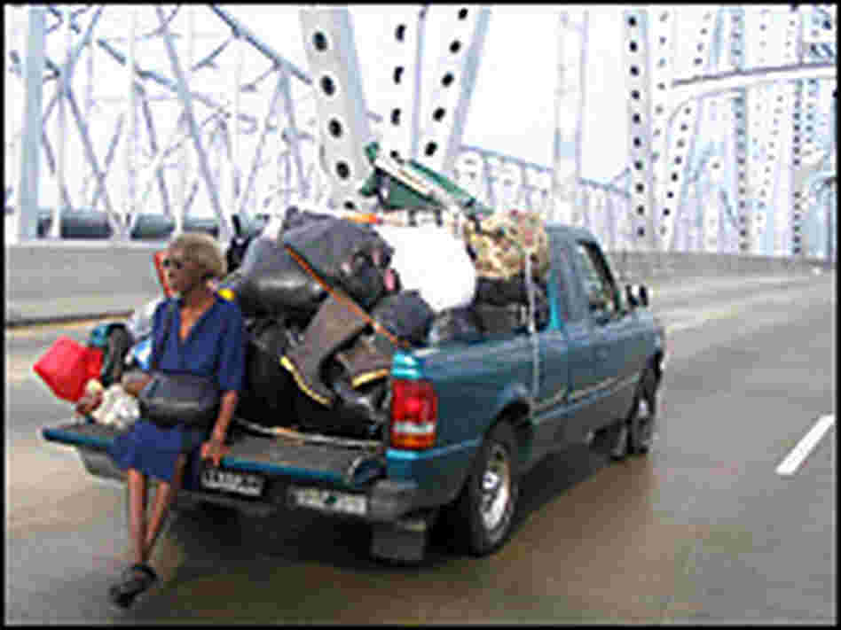 A woman sits on the back of a stranded pick up truck on a bridge. Credit: John Burnett, NPR.