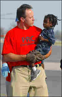A child is carried by a rescue operations worker at New Orleans International Airport, Sept. 4, 2005