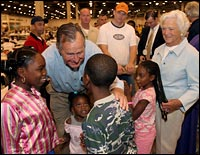 Former President George H.W. Bush and first lady Barbara Bush visit evacuee children during a tour of Reliant Hall adjacent to the Astrodome.