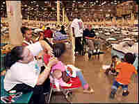 Volunteer Melissa Jackson braids the hair of evacuee Traviell Barra of New Orleans. Credit: Reuters.