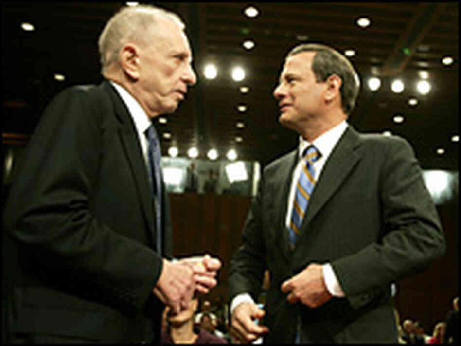 Chief justice nominee John Roberts listens to Senate Judiciary Committee chairman Arlen Specter.