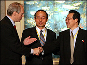 U.S. Assistant Secretary of State Christopher Hill (L) shakes hands with North Korea's chief negotia
