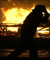 A firefighter struggles to stay upright near burning buildings in Galveston, Texas, as Hurricane Rita approaches, Sept. 23 2005.