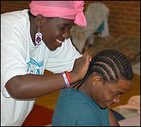 Joquita Stevens braids her brother Don's hair at a shelter in Austin. The family has been there since fleeing Hurricane Katrina.