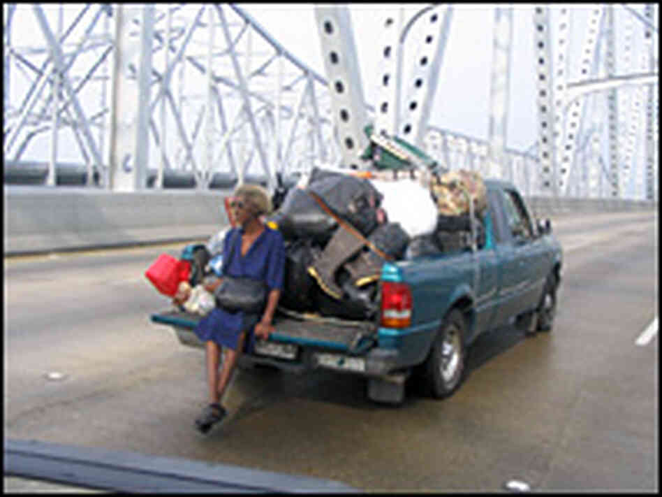 A woman sits on the rear of her truck on a bridge in the aftermath of Hurricane Katrina.