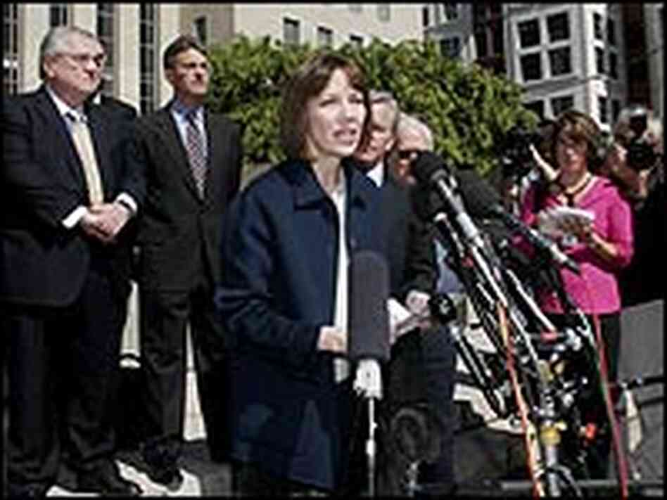 Judith Miller in front of a bank of microphones, surrounded by lawyers.