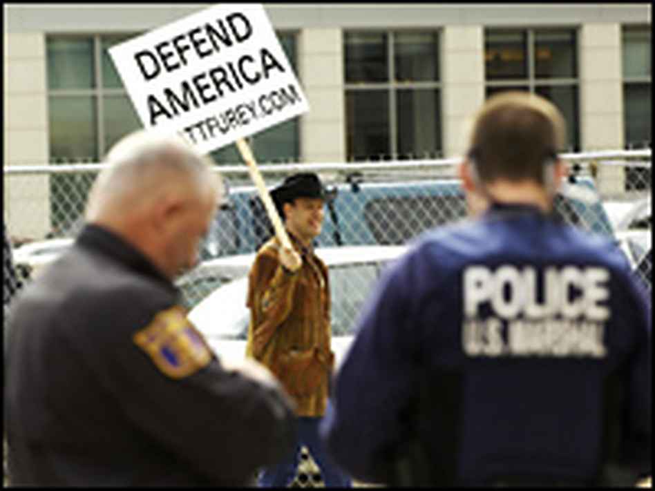 """A lone protestor carries a placard while shouting """"defend America from the terrorists"""" as police stand guard at the Bryan U.S. District Court in Alexandria, Va."""