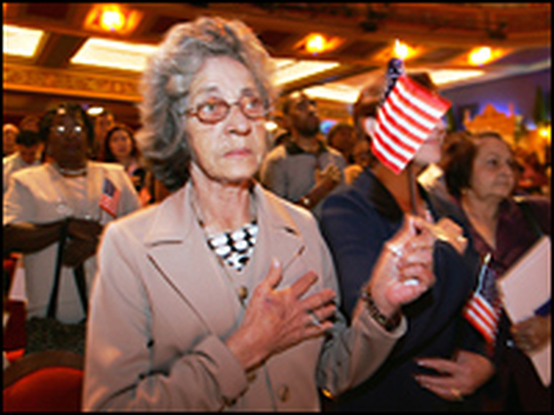 A woman holds a U.S. flag as she and some 250 others take part in a naturalization ceremony in Miami, Fla.
