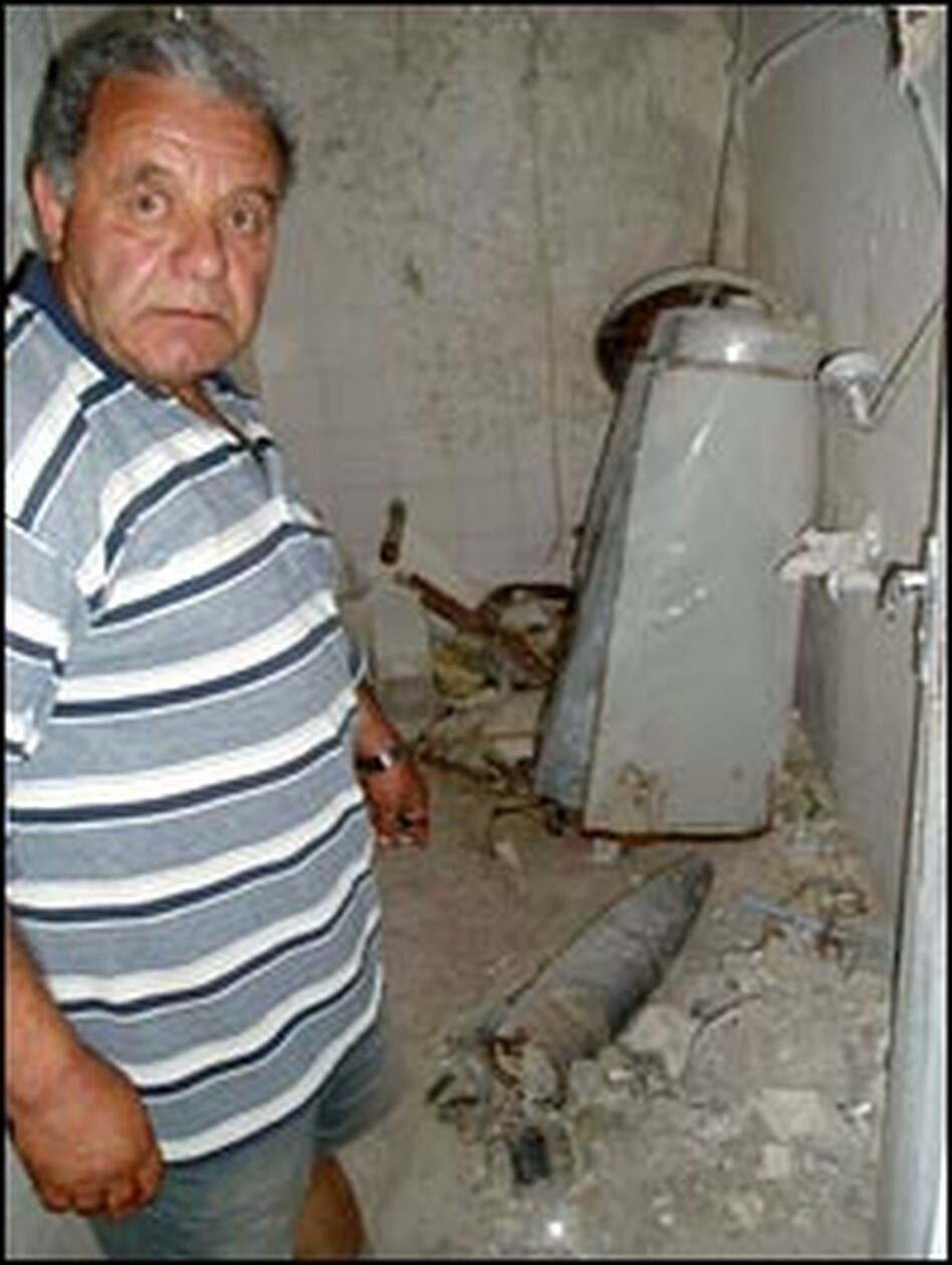 George Hasrooni shows the unexploded Israeli artillery shell lying in the bathroom of his house in Ein Ebel, a Christian village located a few miles from the Israeli border.