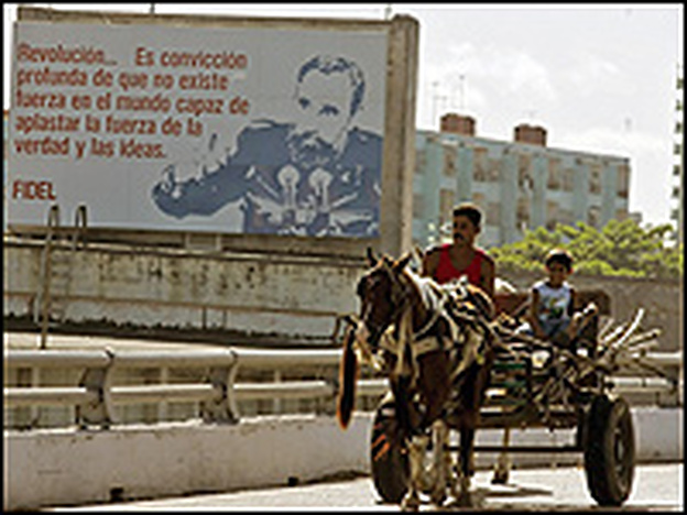 A man and a boy drive their horse cart close to a poster of Cuban President Fidel Castro in Havana.