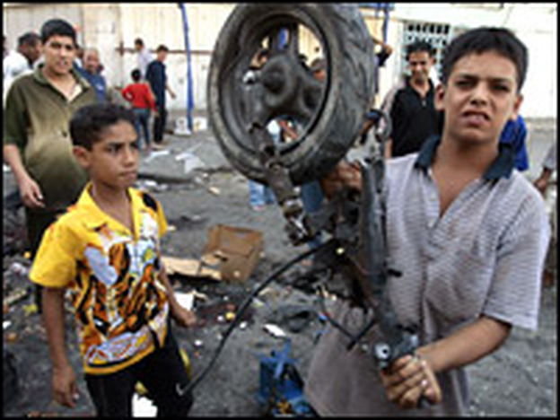 An Iraqi youth carries the wreckage of an explosives-laiden scooter which blew up in Baghdad's Shorjah marketplace. Ten people were killed and 20 wounded in the blast.