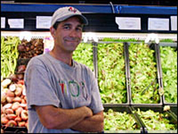 Missoula farmer Josh Slotnick stands in front of a bin of his Montana homegrown salad greens.