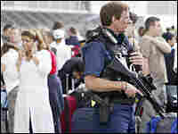 A policeman secures the area as passengers wait at Heathrow airport in London.