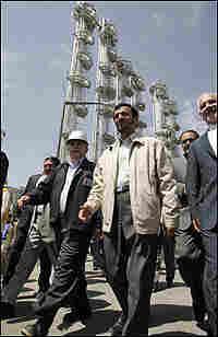 Iranian President Mahmoud Ahmadinejad (C) walks during the opening ceremony of a heavy water plant.