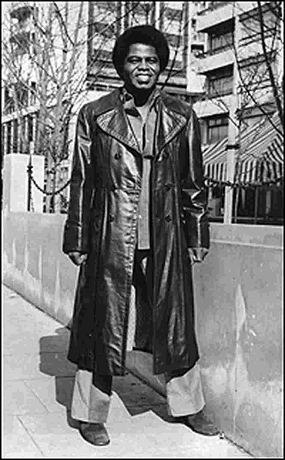 Brown stands on a street wearing a long leather coat.