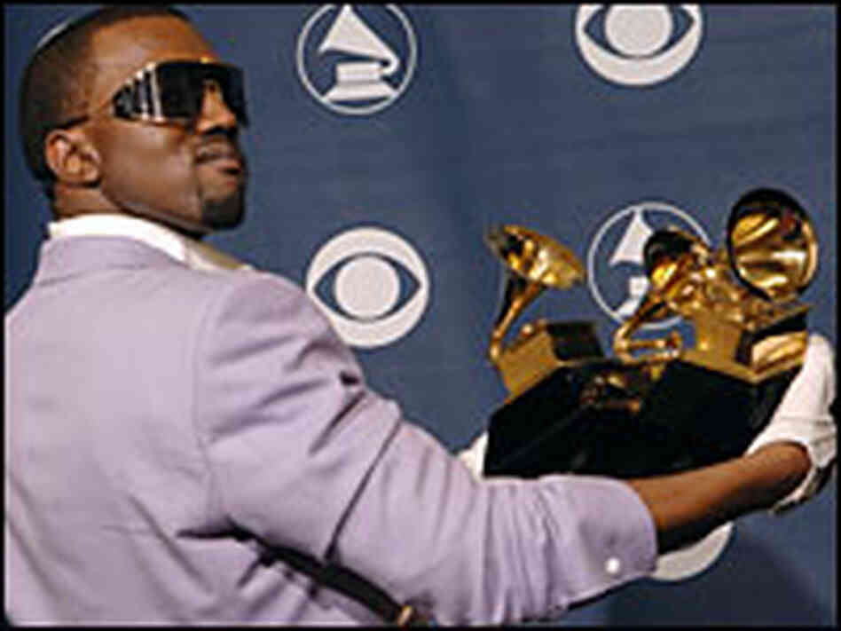 Kanye West holds an armful of Grammy awards.
