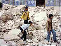 Iraqi Shiites walk on the rubble of the damaged al-Hadi Shiite shrine