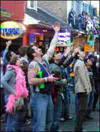 Crowds along Bourbon Street hail fellow revelers in balconies above.